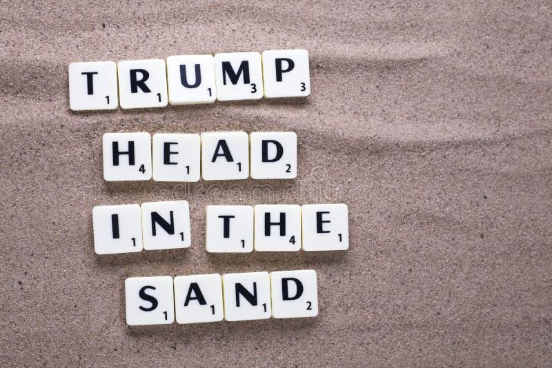 Trump голова в письмах песка на пляже стоковые изображения