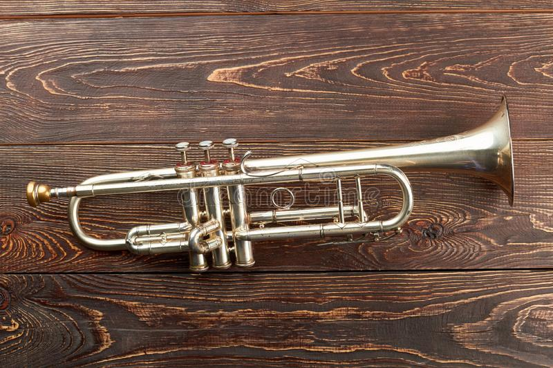 Trumpet on brown wooden background. royalty free stock images