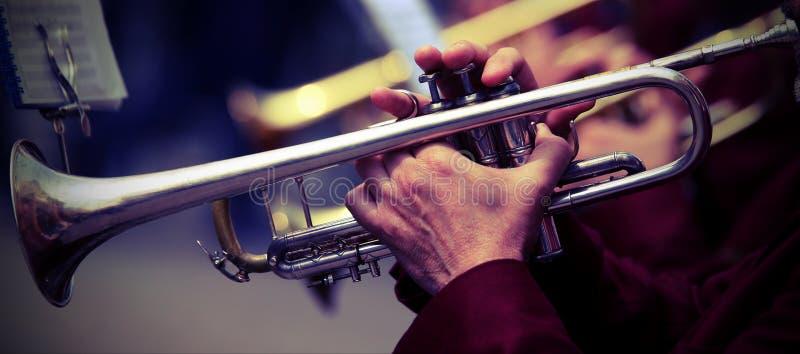 trumpeter παίζει τη σάλπιγγά του στη ζώνη κατά τη διάρκεια της ζωντανής συναυλίας στοκ φωτογραφίες