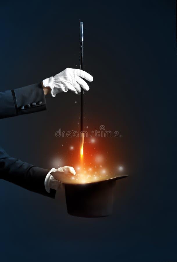 Truque da exibição do mágico com o chapéu no fundo escuro imagens de stock royalty free