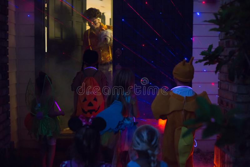 Truque de Dia das Bruxas e das crianças ou tratamento da porta indo à porta na noite imagens de stock