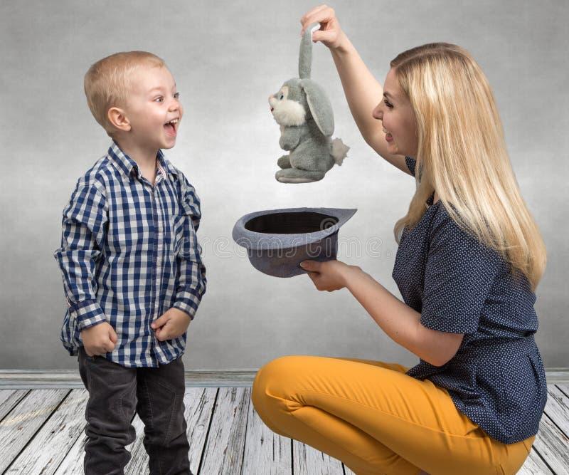 Truques com um coelho Uma mãe nova mostra a rapaz pequeno o coelho dos truques mágicos no chapéu Família amigável, entretenimento fotografia de stock royalty free