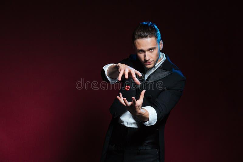 Truques de conjuração concentrados do mágico do homem novo com dados vermelhos fotos de stock royalty free