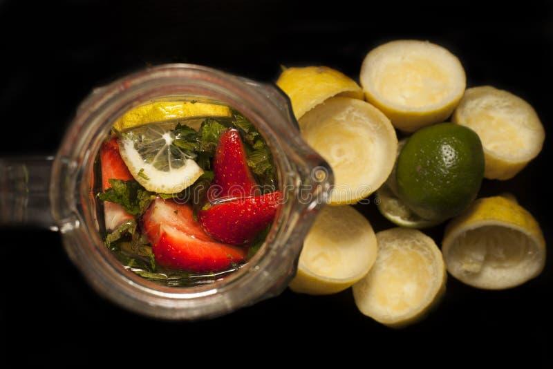 Truskawek cytryn wapna mennicy lemoniada w słój od, słoju lub butelka żółtych cytryn i zielonego wapna z lodem lub zdjęcie stock