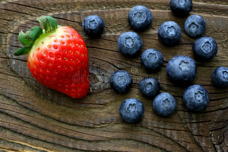 Truskawka i czarne jagody na antykwarskim drewnianym stole zdjęcie stock