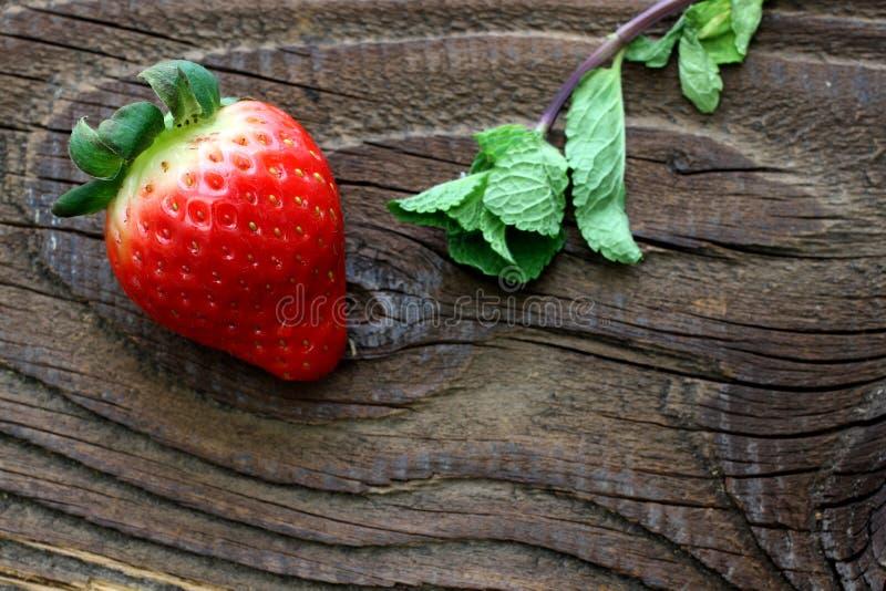 Truskawka i niektóre nowi liście na antykwarskim drewnianym stole zdjęcia royalty free