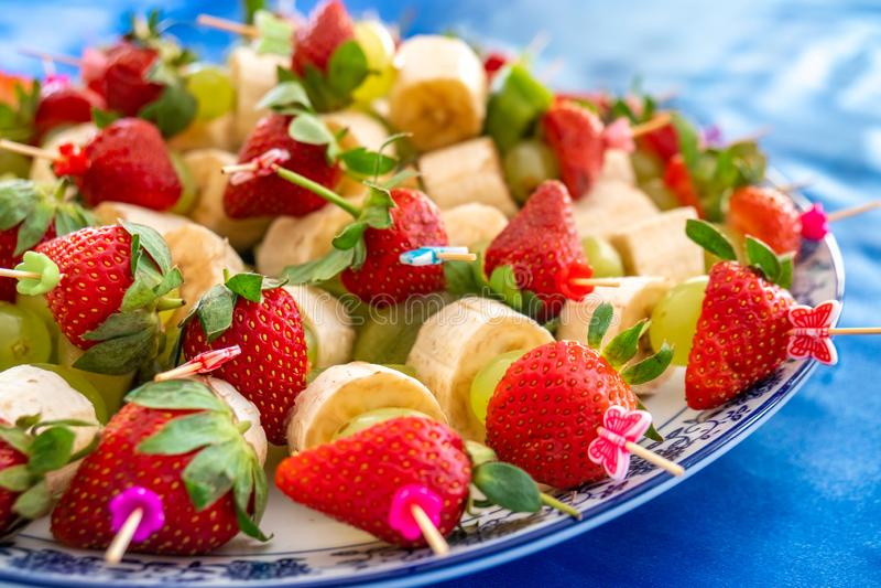 Truskawki i inne egzotyczne owoc przyczepiający z kijami obraz stock