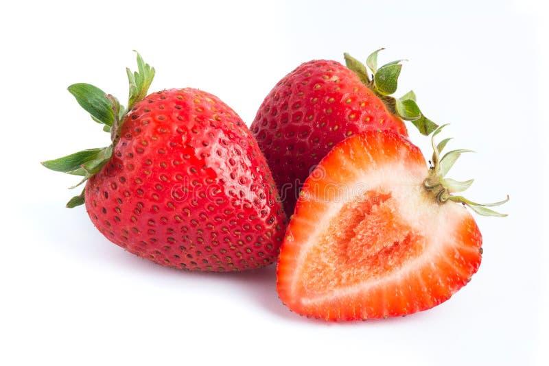 Truskawki owocowe na białym tle z jeden ono jest ciącym połówką zdjęcia royalty free