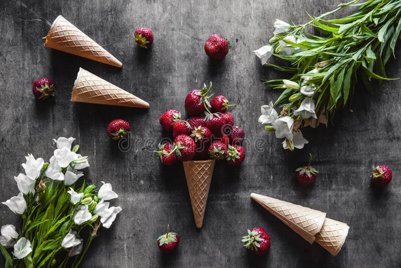 Truskawki w filiżankach na zmroku - szary tło z goframi i białymi kwiatami Zdrowy jedzenie, owoc obrazy royalty free