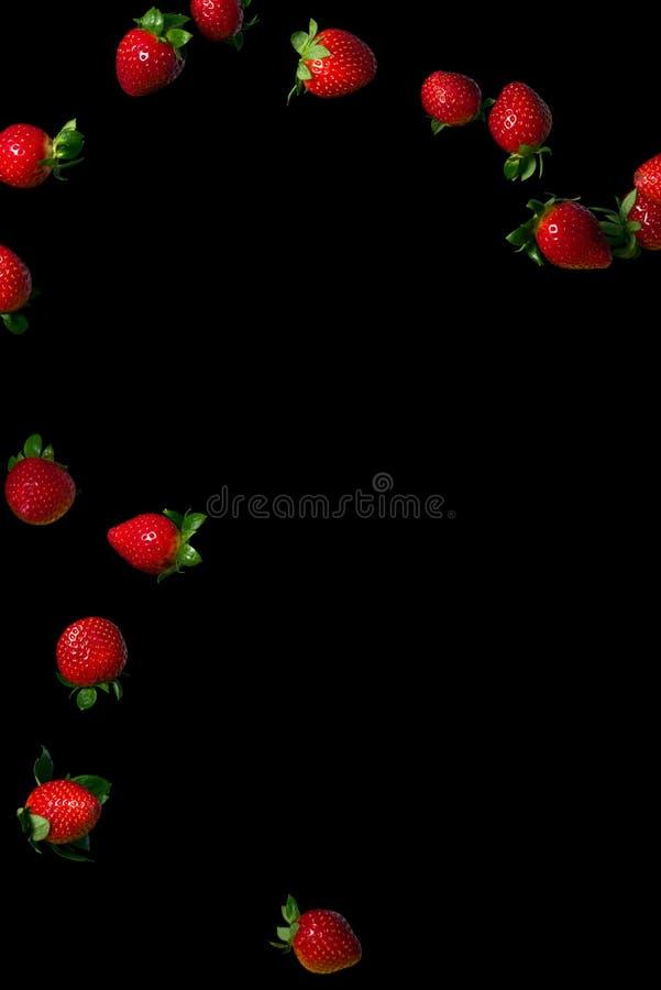 Truskawki w powietrzu Soczyste dojrzałe jagody na czarnym tle obraz stock