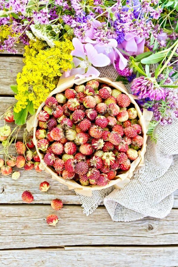 Truskawki w pudełku z kwiatami na pokładzie wierzchołka zdjęcie royalty free