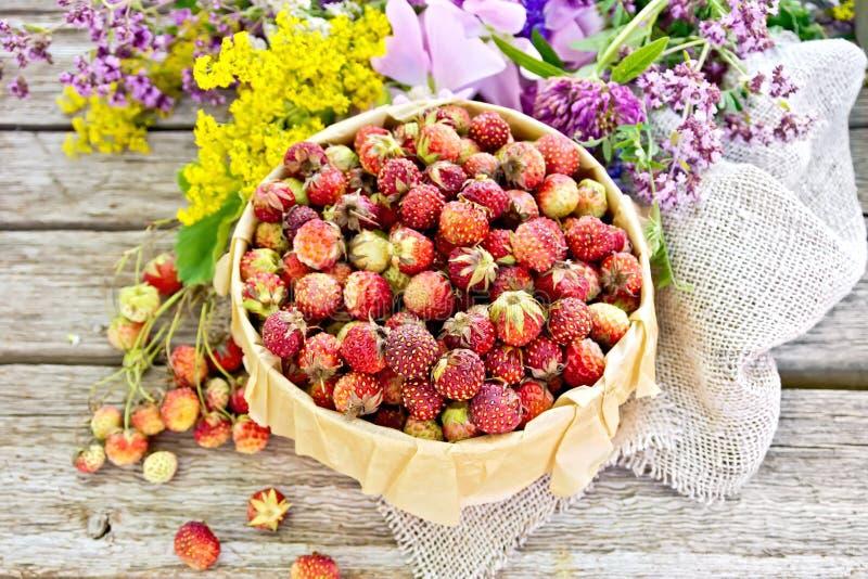Truskawki w pudełku z kwiatami na starej desce zdjęcie royalty free
