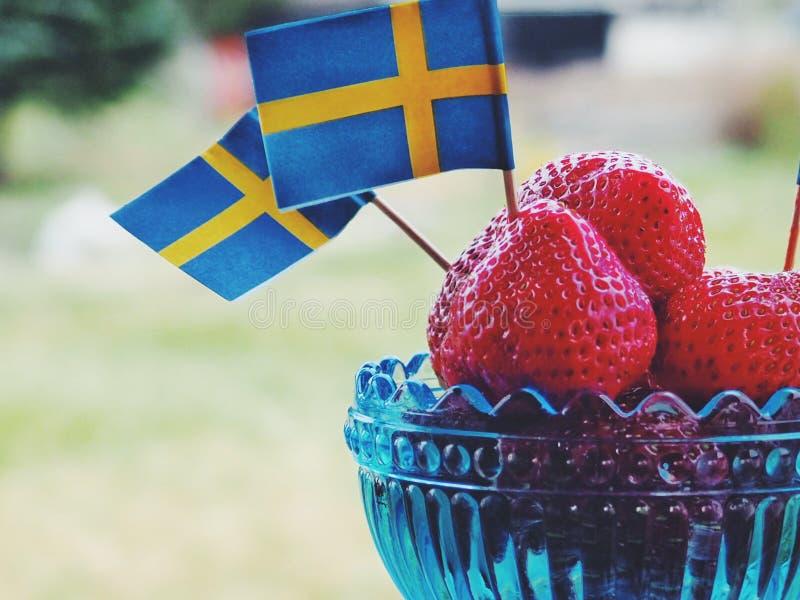 Truskawki z Szwedzkimi flagami Świętowanie Swedens pełnia lata lub święto państwowe obraz stock