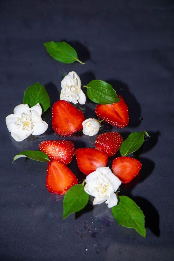 Truskawkowe jagody kłamają na ciemnym tle, obok zielonych liści i białych jaśminowych kwiatów zdjęcie royalty free