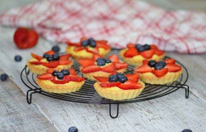 Truskawkowi shortcake kulebiaki na nieociosanym drewnianym stole Ciasto S?odcy tartlets deserowi zdjęcie stock