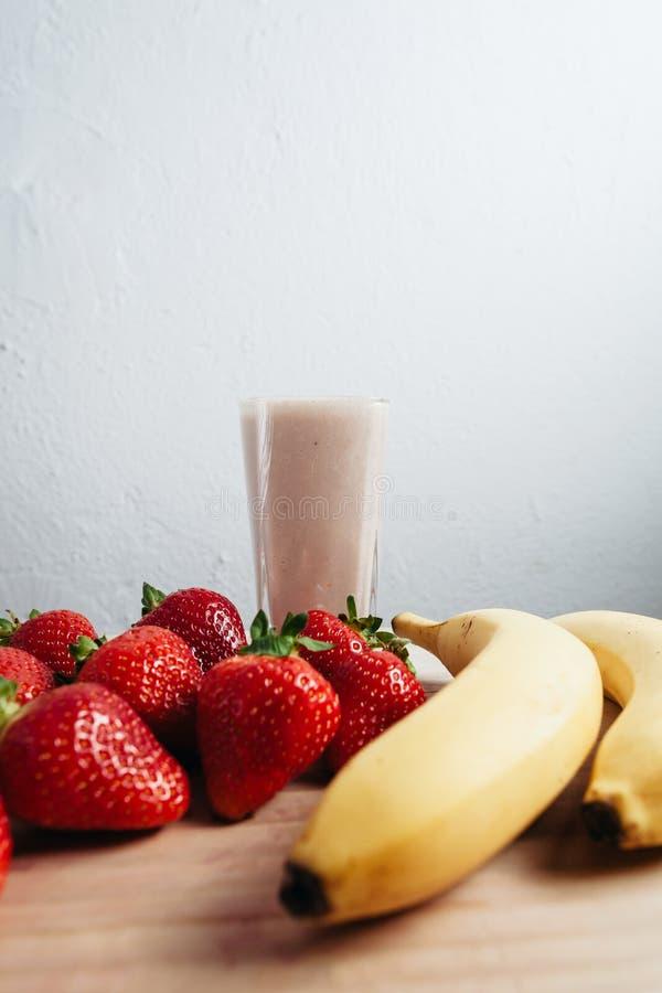 Truskawkowy bananowy smoothie świeży mieszający na drewno stole obraz stock
