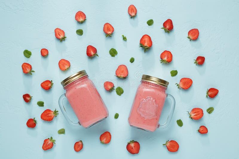 Truskawkowy milkshake w dwa szklanych kamieniarzów słojach na pastelowym błękitnym tle zdjęcia stock