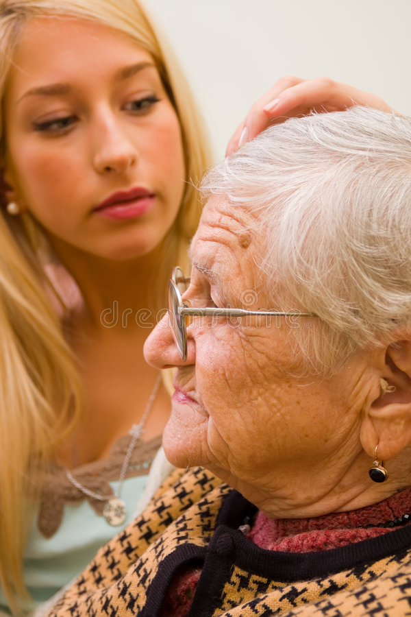 Trust. A young woman stroking an older one whit trust and empathy (focus on the old woman) - part of a series stock photography