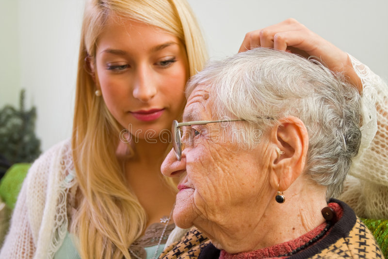 Trust. A young woman stroking an older one whit trust and empathy (focus on the old woman) - part of a series royalty free stock photos