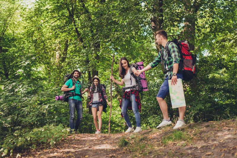 Trust, love, support, help, friendship concept. Four friends are hiking in the spring woods, the guy is holding lady`s hand, all a stock photography