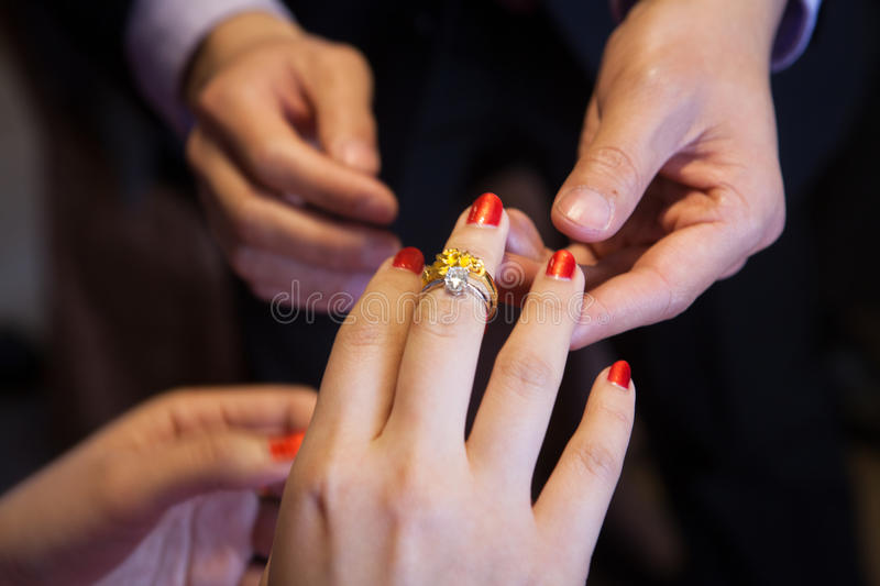 Trust and love. Wedding couple exhanges rings for promise of marriage with trust and love stock photography