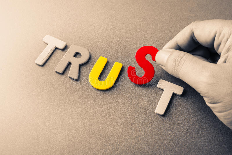 Trust Us. Hand arrange wood letters as Trust word with color letters of Us word inside stock photo