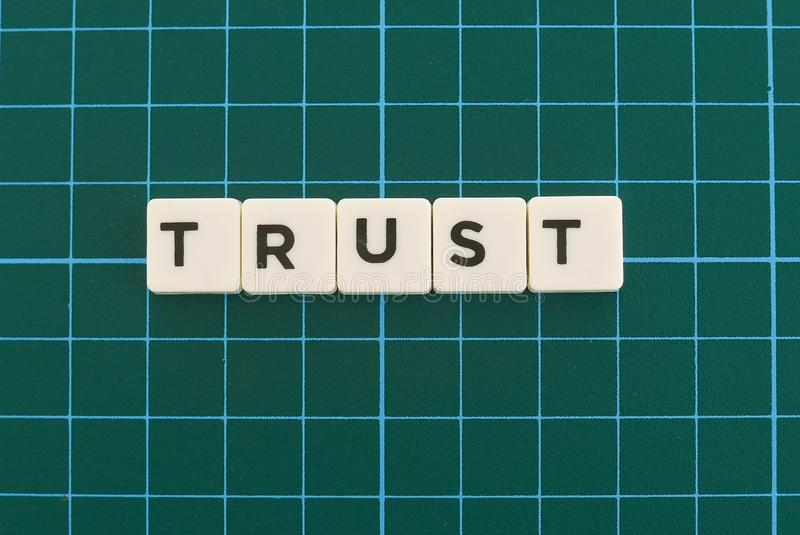 Trust word made of square letter word on green square mat background. Relationship faith loyalty assurance confidence belief business truth text trustworthy stock photography