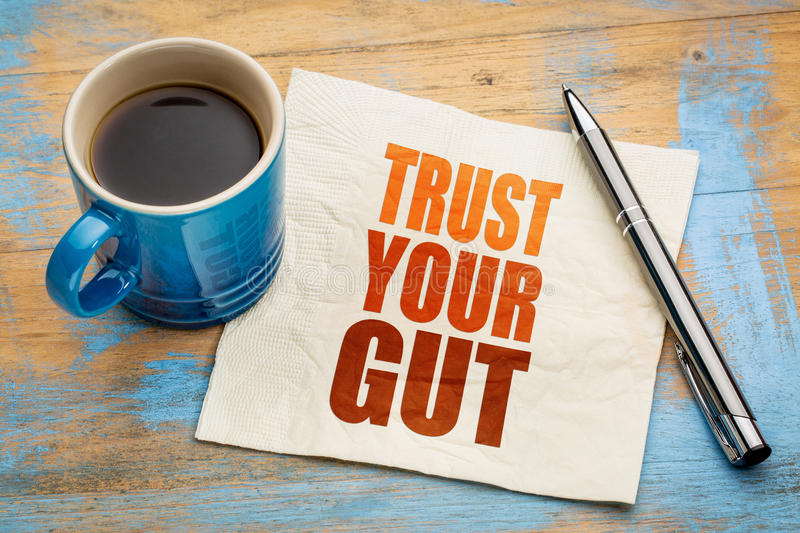 Trust your gut word abstract. Advice or motivational reminder on a napkin with cup of espresso coffee stock images