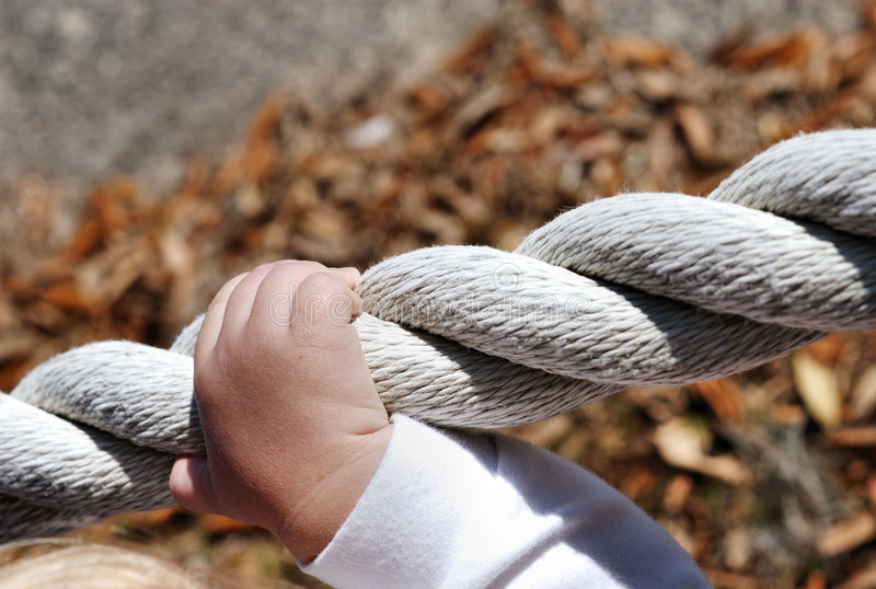Trusting hands on a rope. A child''s hand gripping onto a rope boundary stock photography