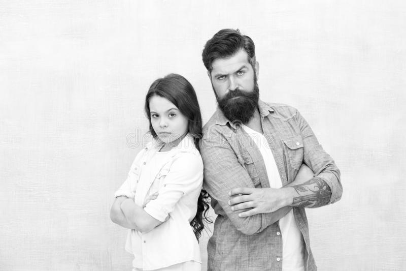 Trusting relations. Little daughter and father keeping arms crossed on grey background. Bearded man and small child royalty free stock image