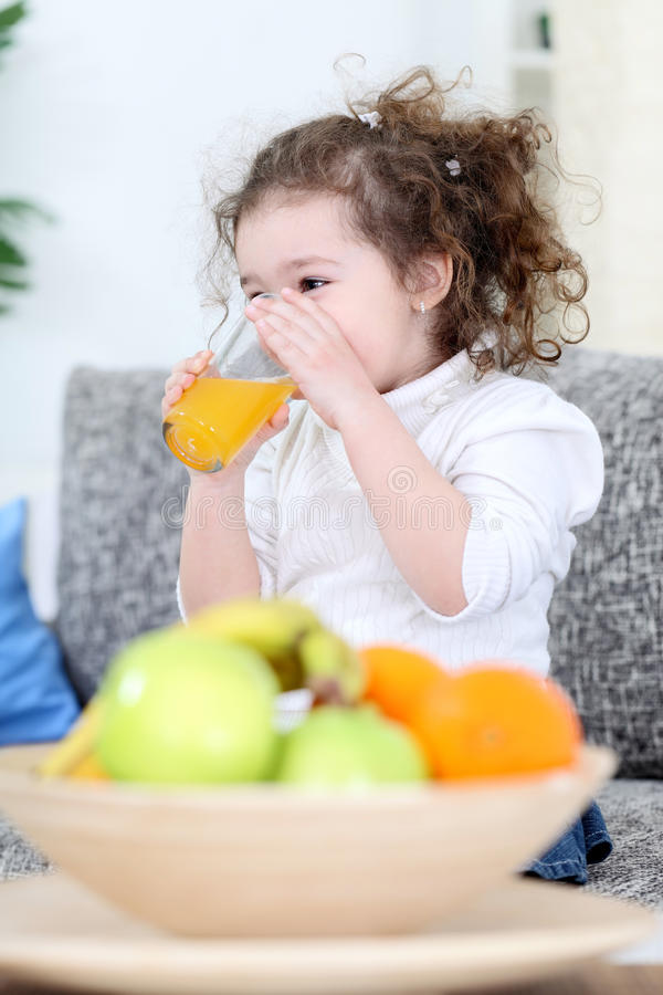 Trusty little girl. Drinking fresh juice royalty free stock images