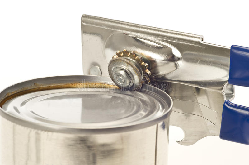Trusty Old Can Opener. A can being opened by the trusty old can opener stock image