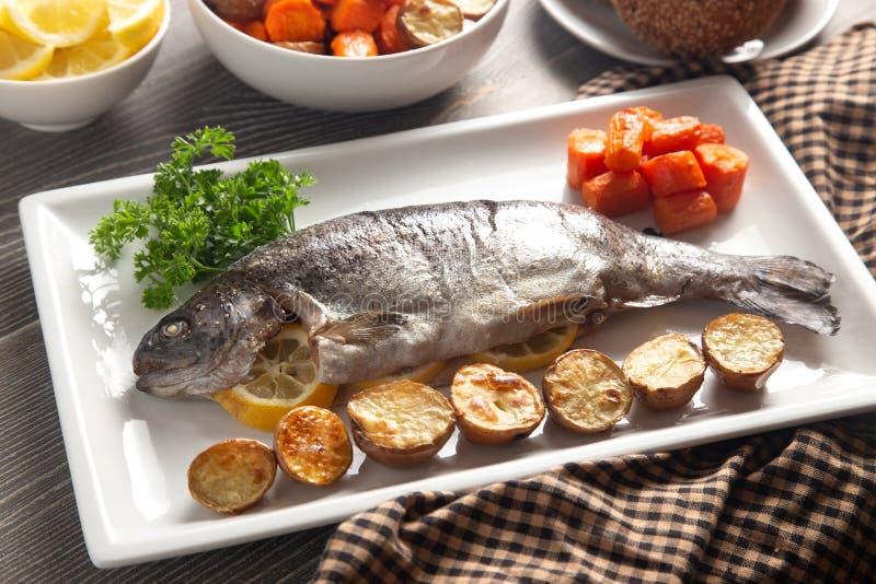 Truta arco-?ris cozida inteira em uma tabela ajustada para o jantar foto de stock royalty free