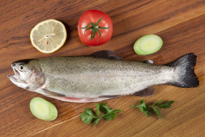 Truta estripada dos peixes em uma placa de corte imagens de stock royalty free