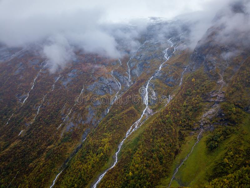 Truteń fotografia Kilka Małe siklawy w górach z chmurami Zakrywa one Blisko Bøjabreen lodowa w Norwegia obraz royalty free