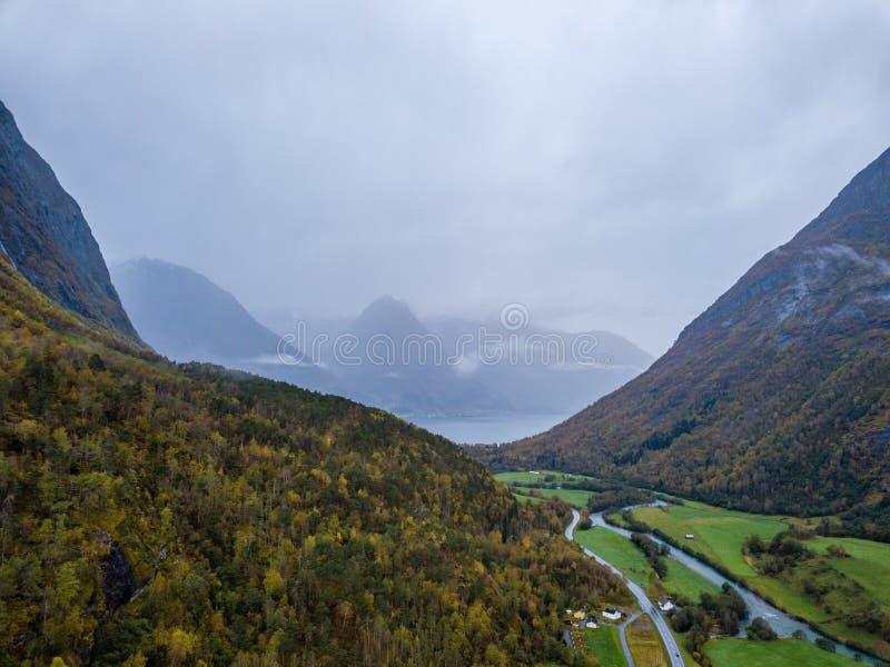 Truteń fotografia lasy w górach i Rzeczny Hjelledøla w Folva, Norwegia z chmurami Zakrywa góry zdjęcie stock