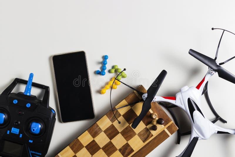 Truteń, pilot do tv, chessboard, szachy, telefon komórkowy na białym tle Chłopiec czas wolny bawi się pojęcie Odgórny widok Miesz fotografia stock