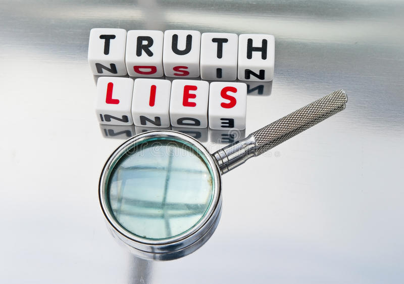 Truth and lies. Text 'truth and lies' inscribed in uppercase letters on small white cubes in black and red colors respectively , hand magnifier beside to stock photo
