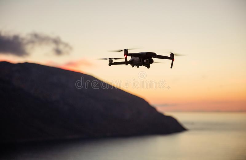 Trutnia quadcopter z cyfrową kamerą lata nad wybrzeżem przy zmierzchem zdjęcie stock