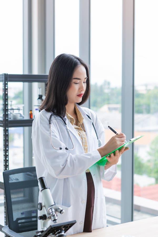 Trwanie azjatykcia żywiona doktorska kobieta pisze na papier zieleni desce w laboranckim pokoju obrazy stock