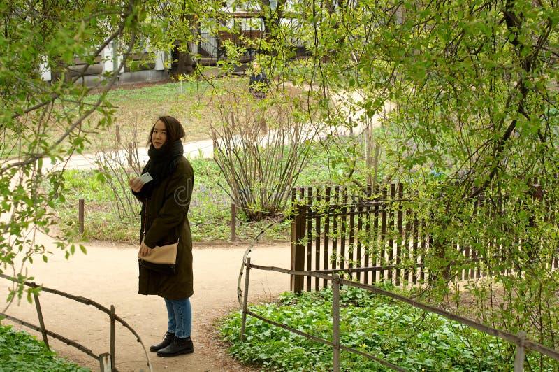 Trwanie dziewczyna z telefonem w parku zdjęcia stock