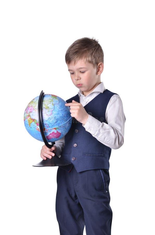 Trwanie uczniowski chwyt kula ziemska świat i gmeranie coś na nim fotografia royalty free