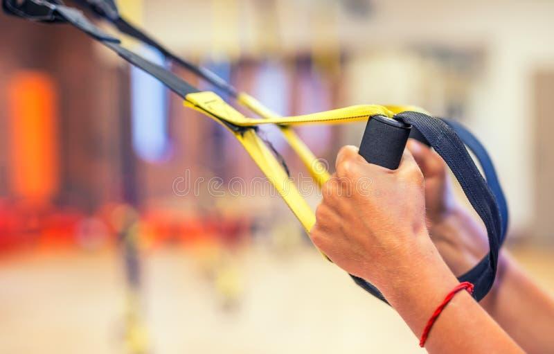TRX Kvinnlighänder med remmar för kondition TRX i idrottshall arkivbilder