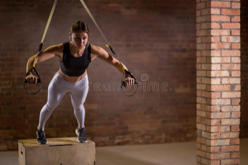 Fitness woman workout on TRX straps in gym. Crossfit style. Training TRX. stock photo