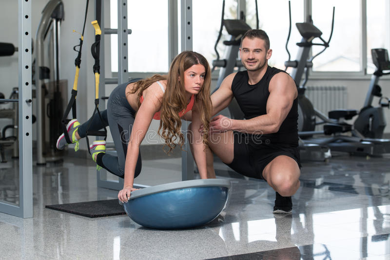 Trx Straps Training. Personal Trainer Showing Young Woman How To Train With Trx Fitness Straps In A Gym stock image