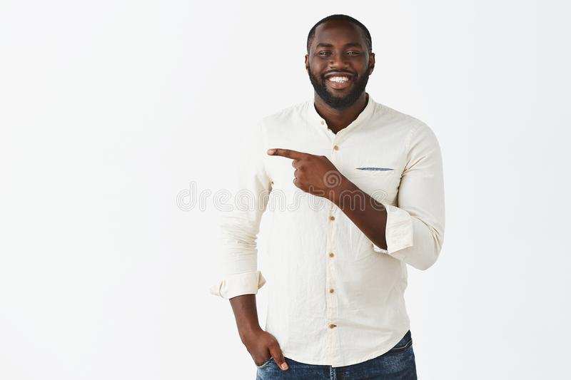 Try that direction. Charming friendly-looking and joyful dark-skinned guy with beard in white shirt, holding hand in. Pocket, standing casually while showing stock image