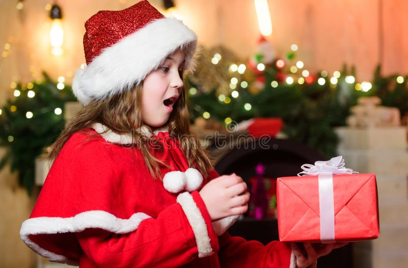 Try it. Happy new year. Elf child. Xmas tree. Happy holiday. Little girl in red hat. Happy christmas. Santa claus little. Girl. Chriatmas interior. Christmas stock photo
