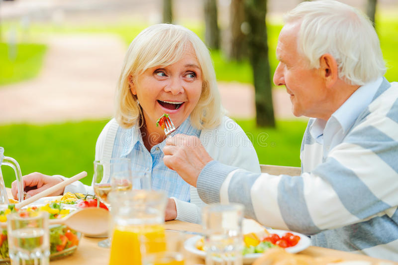 Try my meal!. Senior men feeding his cheerful wife with fresh salad while both sitting at the dining table outdoors stock image