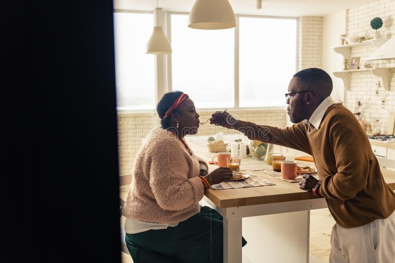 Nice afro American man feeding his beloved wife royalty free stock photos