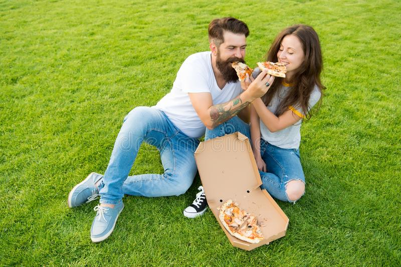 Try this. summer picnic on green grass. couple in love dating. fast food. bearded man hipster and adorable girl eat stock photo
